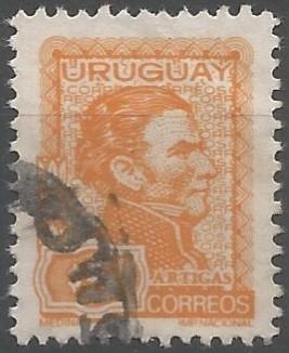 busto de Artigas, representado con el cabello crespo extendido sobre la cara en una larga patilla y chaqueta militar correspondiente al uniforme de Blandengues